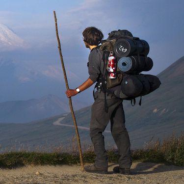 un voyageur sac au dos et bâton à la main